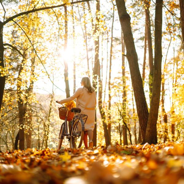 Brustkrebs kurz erklärt: Eine Frau mit Fahrrad im Wald
