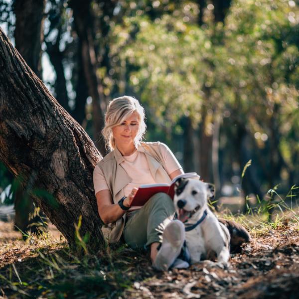 Geheilt aber nicht gesund - eine Frau entspannt mit ihrem Hund unter einem Baum